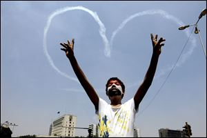 An Egyptian protester flashes v signs as military aircraft formed heart-shaped trails in the sky over Tahrir Square in Cairo on Friday.  Clashes erupted when masses of Morsi supporters tried to enter Liberation Square.