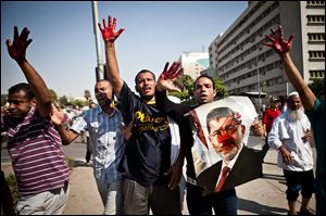 Islamist protesters, one holding a picture of ousted president Mohammed Morsi, hold up blood-stained hands after troops opened fire on a protest.