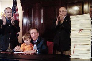 Felix Falco Plouck, 4, the son of a cabinet member, helps Ohio Gov. John Kasich sign the state's two-year budget in Columbus last week. The governor is flanked by state Senate President Keith Faber (R., Celina), left, and House Finance Committee chairman Ron Amstutz (R., Wooster), right.