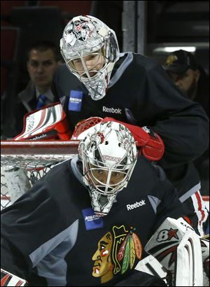 Chicago Blackhawks goalie Corey Crawford, top, watches teammate Ray Emery during an NHL hockey practice Friday, June 21 in Chicago. Emery accepted at $1.65M contract with the Philadelphia Flyers.