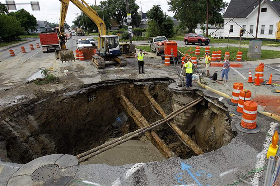 Workers-assess-the-sinkhole-at-Ban