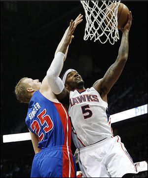 Josh Smith (5) goes up for a basket against Pistons small forward Kyle Singler last season. Smith will be on Detroit's side next season.