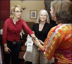 Former Arizona Rep. Gabrielle Giffords greets Jackie Barden, right, mother of a Sandy Hook Elementary School shooting victim Daniel Barden, as local supporter Mary Ann Sosnoff, center, looks on at the Orchard Street Chop Shop in Dover, N.H.