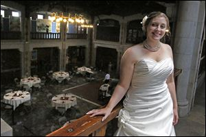 Kristin Rakas, of Bowling Green, stands in the Great Hall of the Toledo Zoo, overlooking the tables set up for her wedding reception.
