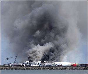 Fire crews work the crash site of Asiana Flight 214 on Saturday at San Francisco International Airport, where two people died.