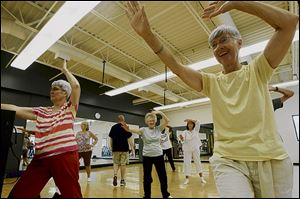 Barbara Laraway, left, Colleen Fisher, center, and Marilyn Hom stretch during a Tai Chi class.
