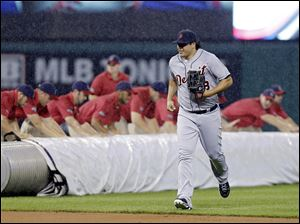Detroit left fielder Matt Tuiasosopo runs for the dugout as the grounds crew rolls out the tarp in a rain delay in the second inning in Cleveland. Tuiasosopo hit a home run in the fourth inning.