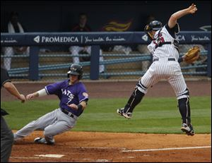 Louisville's Jason Donald scores when Toledo catcher Bryan Holaday is forced off the plate by a high throw.