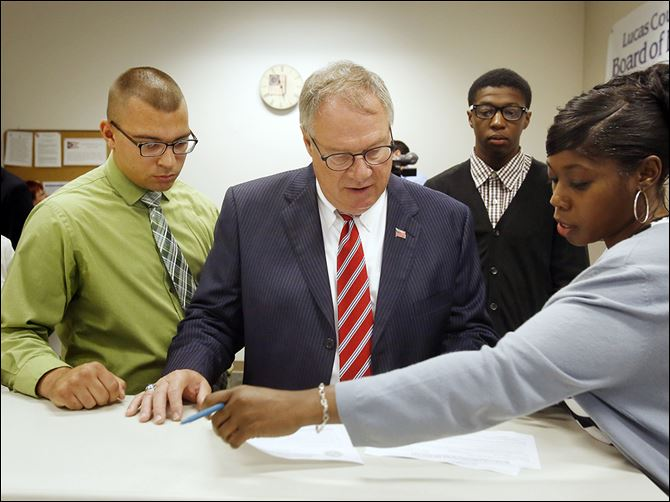 n3collins D. Michael Collins, center, goes over paperwork with campaign co-manager Joe Braun, left, and campaign finance clerk Glynis Fuentes after turning in petition signatures to the Lucas County Board of Elections.