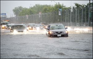A woman gets back in her car in flood water on Lakeshore West during a storm in Toronto today.