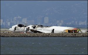 The wreckage of Asiana Airlines Flight 214 that crashed upon landing Saturday at San Francisco International Airport sits on the tarmac Monday, July 8, 2013 in San Francisco. Investigators said the Boeing 777 was traveling