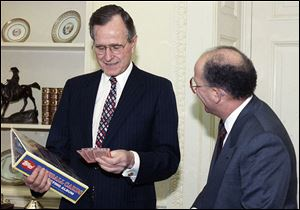 President George H.W. Bush, shown in this 1990 photo, jokes with Arthur Shorin, president of Topps Co., Inc., after Shorin presented him a book of baseball cards. The cards depicting the former president as a Yale first baseman have fetched thousands of dollars.