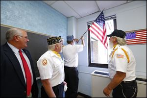 State Rep. Dale W. Zorn of Ida, left, watches as James Walker, commander of the Monroe County Disabled American Veterans; Larry Brossia, of the Sons of American Legion Squadron 72, and Richard Cummings, commander of American Legion Post 72, hang a flag at Dundee Middle School.