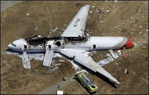 Tthe wreckage of Asiana Flight 214 lies on the ground after it crashed at the San Francisco International Airport.