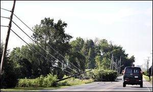 Vehicles avoid downed power lines that litter State Rt. 53 near Tiffin. Hundreds of customers were without electricity throughout the region after the storm.