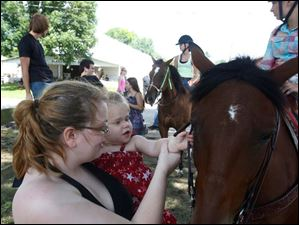 Rachel Kimple, of West Toledo, left, helped her niece Lilly Laraby, 9 months-old, pet Bonnie, an 11 year-old Quarter Horse ridden by Gracyn Amos, 12.