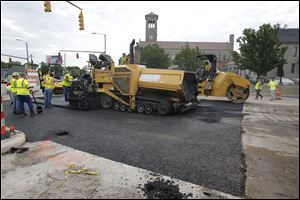 Workers from Ebony Construction Company of Sylvania pave North Detroit Avenue at W. Bancroft Street today. The road reopened today after the sinkhole was repaired.