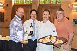 From left, Christopher Knapik and Kevin Boehm of Berman Wines with Chef Sam Misuira and Toledo Zoo executive director Jeff Sailer at the zoo's preview party food tasting for the upcoming FEAST with the beasts.