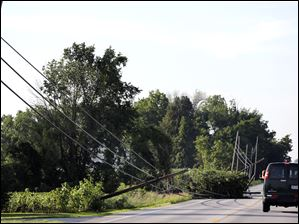 Vehicles avoid downed power lines after a powerful storm Wednesday on State Route 53 in Tiffin.