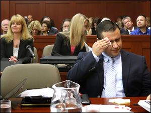 George Zimmerman wipes his face today after arriving in the courtroom during his trial at the Seminole County Criminal Justice Center.