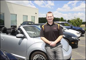 Tim Gladieux, Volkswagen sales manager at Ed Schmidt Volkswagen, stands by  a Beetle convertible. GM hasn't sold a diesel-powered passenger car in more than 20 years, and Mr. Gladieux said the Volkswagen Passat TDI has sparked more interest in diesel.