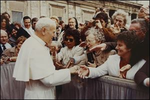Sister Marie Andree Chorzempa, 86, center, shakes hands with Pope John Paul II in Rome in 1985.