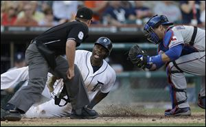 Umpire Quinn Wolcott, left, looks on as Detroit Tigers' Torii Hunter, center, scores under the tag of Texas Rangers catcher A.J. Pierzynski on Tigers' Victor Martinez's double to left field during the second inning Friday.