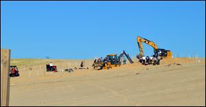 Michigan City firefighters, police, and first responders dig through a sand dune at Mount Baldy near Michigan City, Ind., while searching for a missing 6-year-old-boy who fell into a hole Friday.