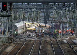 Railways workers are seen at the site where a train derailed Friday, at a station in Bretigny-sur-Orge, south of Paris, today.