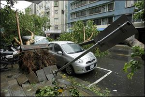 Fallen trees damaging vehicles lie on a street after Typhoon Soulik hit Taiwan early today in Taipei.