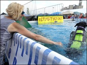 Susan Swalius helps to get a labrador mix named Brynn used to the water.