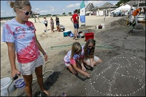 Maumee Bay Lodge team Kylee Ault, 19, left, Jamie Burchell, 26, center, and Alana Snow, right, 19, create a turtle sandcastle for the sand castle contest.