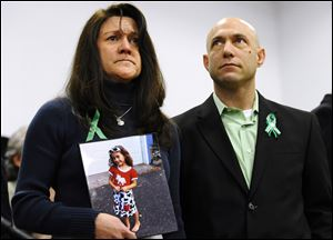 Jennifer Hensel, holding a portrait of her daughter, Sandy Hook School shooting victim Avielle Rose Richman, stands with her husband Jeremy Richman at a news conference at Edmond Town Hall in Newtown, Conn.
