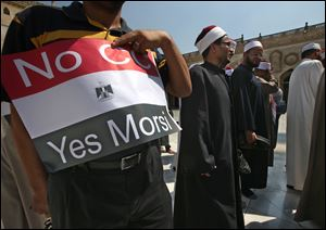 An Egyptian supporter of ousted Egyptian President Mohammed Morsi holds up a placard against Egyptian Defense Minister General Abdul Fatah al-Sisi as he leaves with clerics following a protest Sunday at al-Azhar mosque in Cairo. Egypt's military chief has defended the ouster of the Islamist president, saying he acted upon the will of the people after the