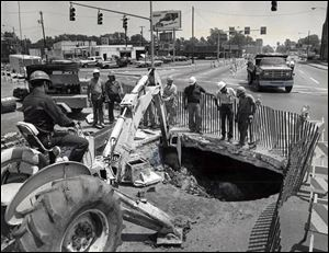 Street crews confronted by city's big 'hole-in-one' . City workers stare into what looks like a bottomless pit at West Bancroft Street and Detroit Avenue Wednesday June 27, 1979 durinheir efforts to repair the hole, caused by the collapse of an old sanitary sewer. As workers were attempting to clean up