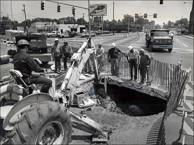 sinkhole14p.jpg Street crews confronted by city's big 'hole-in-one' . City workers stare into what looks like a bottomless pit at West Bancroft Street and Detroit Avenue Wednesday June 27, 1979 durinheir efforts to repair the hole, caused by the collapse of an old sanitary sewer. As workers were attempting to clean up