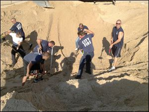 FILE - In this July 12, 2013 file photo, Michigan City police and firefighters dig with shovels to rescue Nathan Woessner, of Sterling, Ill., who was trapped for more than three hours under about 11 feet of sand at Mount Baldy dune near Michigan City, Ind. On Monday, July 15, the doctor who helped treat the 6-year-old boy says the child is expected to make a full neurological recovery. (AP Photo/Michigan City Fire Department via The News Dispatch, File)