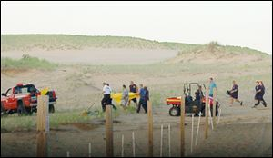 In this July 12, 2013, photo rescue workers with a stretcher carrying 6-year-old Nathan Woessner after he was pulled from a sand dune at the Indiana Dunes National Lakeshore in Michigan City, Ind. Doctors said Monday, July 15, that the boy, who was buried for hours the sand dune, is responsive and expected to make a full neurological recovery. (AP Photo/The News Disparch, Julie McClure)