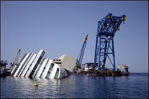 The Costa Concordia Ship wreck lies on its side in the Tuscan Island of Isola del Giglio. Salvage crews are working against time to right and remove the shipwrecked Costa Concordia cruise ship, which is steadily compressing down on itself from sheer weight onto its granite seabed perch.