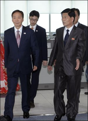 Kim Kiwoong, left, the head of South Korea's working-level delegation, and his North Korean counterpart Park Chol Su, right, enter a meeting room at Kaesong Industrial District Management Committee in Kaesong, North Korea, today.