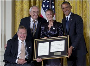 President Barack Obama, right, with former President George H. W. Bush, left, present the 5,000th Daily Point of Light Award to Floyd Hammer and Kathy Hamilton, center, from Union, Iowa, in the East Room of the White House on Monday in Washington.