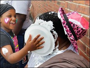 Phyllis Barner, 7, puts a pie in the face of Owens Corning intern Moshood Olowu, 27, during the 5th Annual Field Day at the Friendly Center of Toledo.