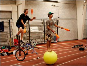 Columbus resident Evan Smith rides a unicycle and juggles along with Andres Ramos of Puerto Rico as he balances on a ball.