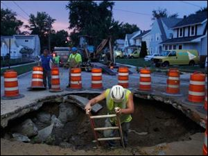 City of Toledo Water Div.  workers secure the hole dug to expose a water main break on the corner of Grantwood and Yellowstone streets.