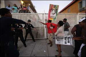 Protesters confront Los Angles police officers during a demonstration in reaction to the acquittal of neighborhood watch volunteer George Zimmerman.