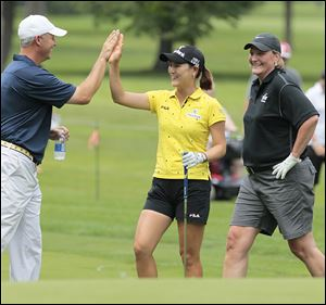 UT golf coach Jamie Broce high-fives playing partner So Yeon Ryu, who won last year's Farr Classic, as UT women's basketball coach Tricia Cullop walks by at the Image Group Celebrity/Pro Challenge.