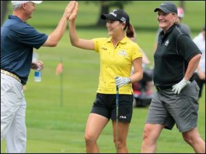 University of Toledo head golf coach Jamie Broce high-fives playing partner and defending champion So Yeon Ryu as women's basketball coach Tricia Cullop, right, laughs during the The Image Group Celebrity/Pro Challenge.
