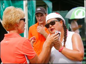 LPGA pro Christina Kim, right, helps Gail Pilmore, of Sylvania, with her cell phone camera during the The Image Gro