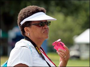 Teri Steward of Columbus, cools off as she watches practice at the Marathon Classic.
