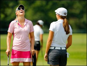 Amanda Blumenherst, left,  jokes with fellow LPGA pro Vicky Hurst as they work on their putting on the practice green Wednesday.